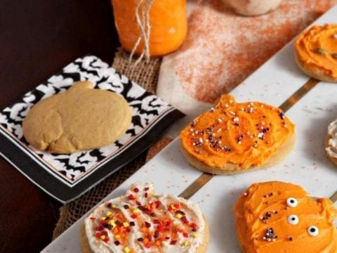A marble platter holds several decorated Spiced Pumpkin Sugar Cookies