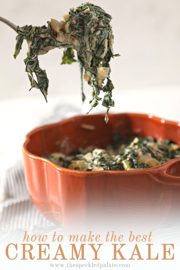 A spoon lifts a spoonful of Creamy Kale out of an orange serving dish that sits on a gray striped towel with the text 'how to make the best creamy kale'
