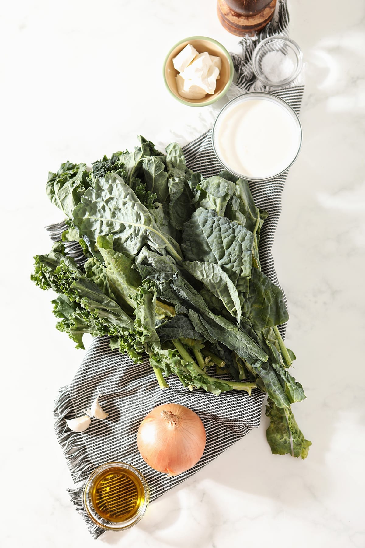 Fresh kale, onion and other ingredients on a gray striped towel