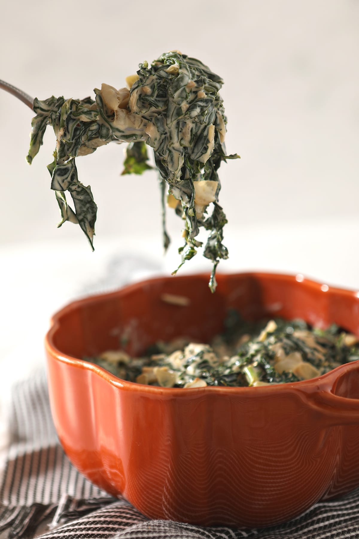 A spoon lifts a spoonful of Creamy Kale out of an orange serving dish that sits on a gray striped towel