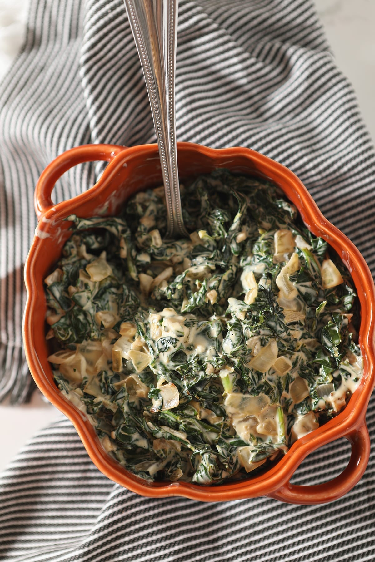 A silver spoon sits in an orange dish of Creamy Kale sitting on a gray striped towel