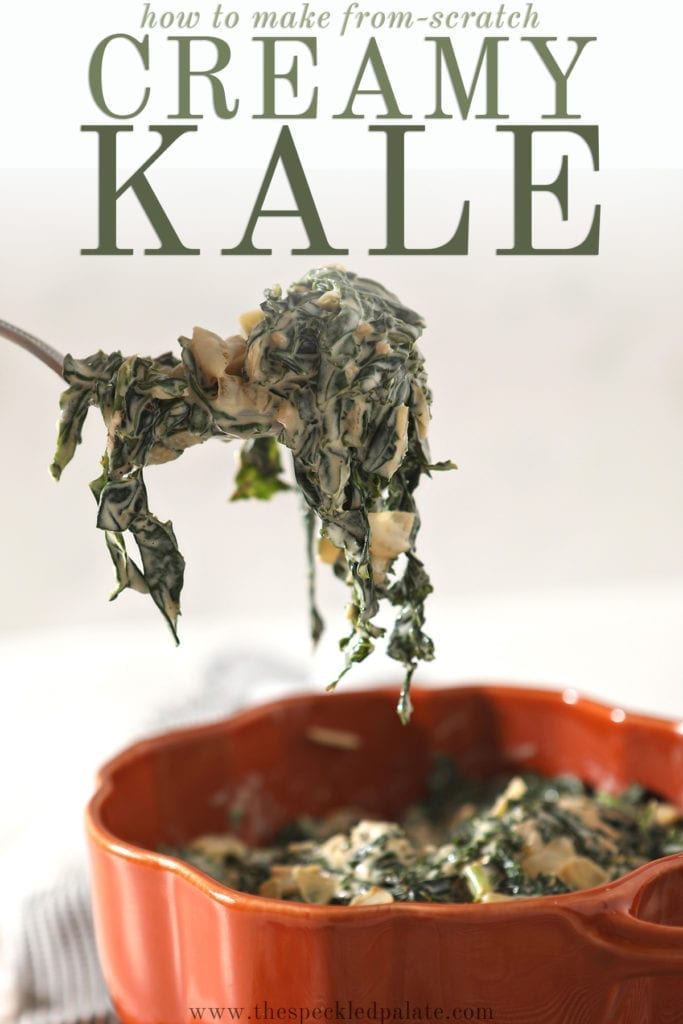 A spoon lifts a spoonful of Creamy Kale out of an orange serving dish that sits on a gray striped towel with the text 'how to make from-scratch creamy kale'