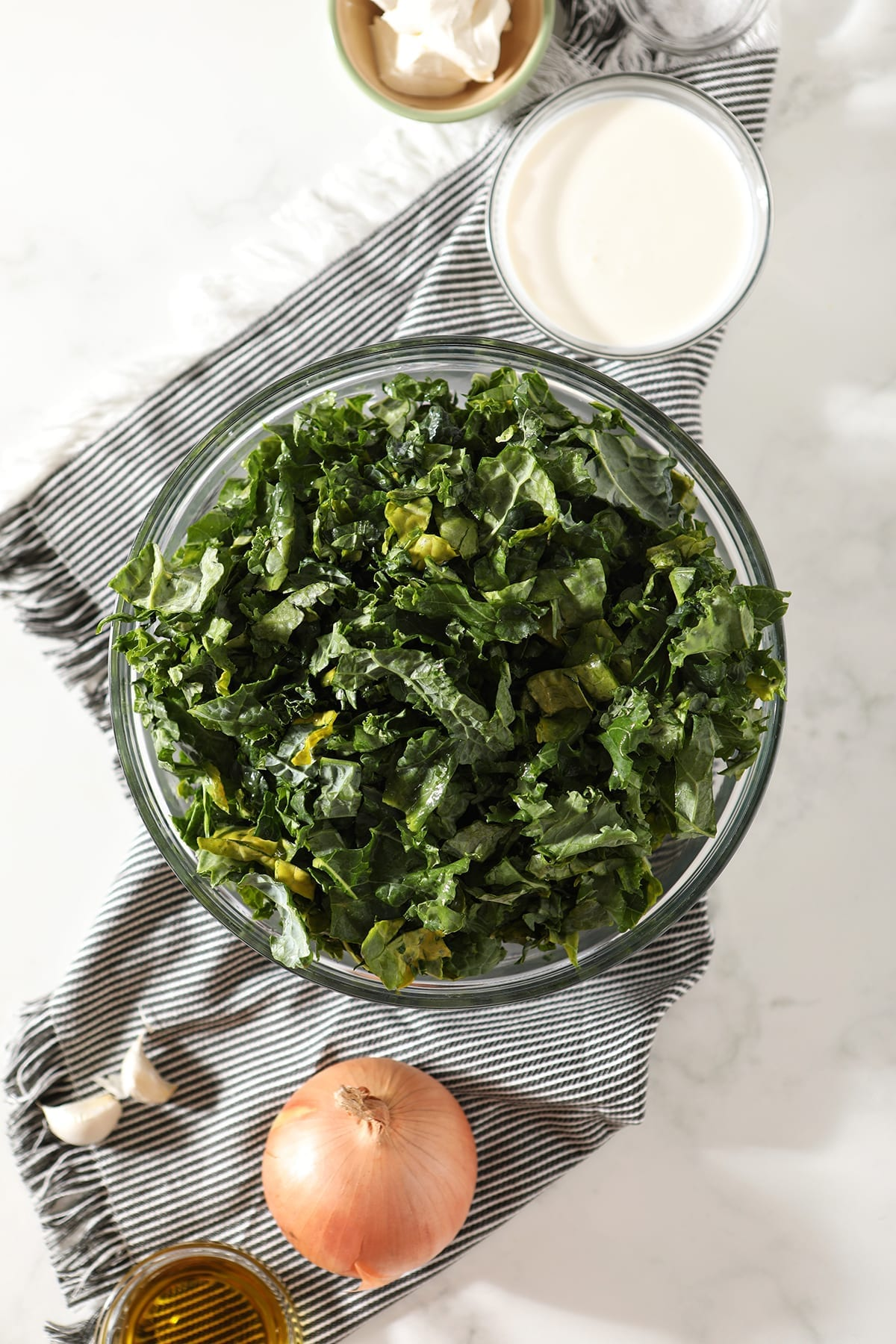 Chopped fresh kale in a bowl sitting on top of a gray striped towel, sitting next to an onion, garlic and other ingredients