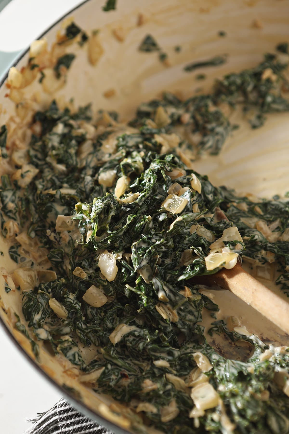 The creamy kale in a pan, after stirring the cream cheese into the mixture