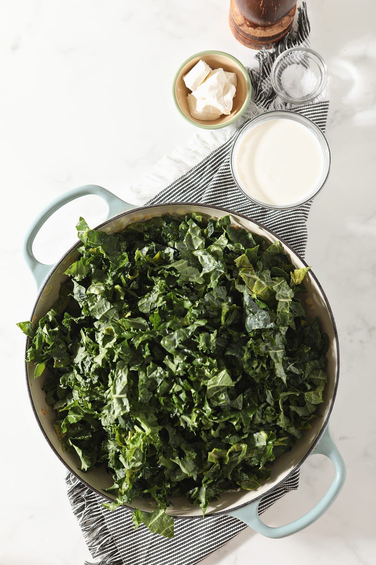 Chopped kale in a braiser pan on a gray striped towel next to cream cheese, cream, salt and pepper
