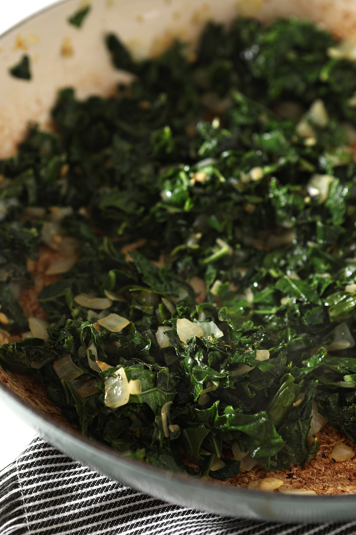 Close up of sauteed kale with onion and garlic in a pan