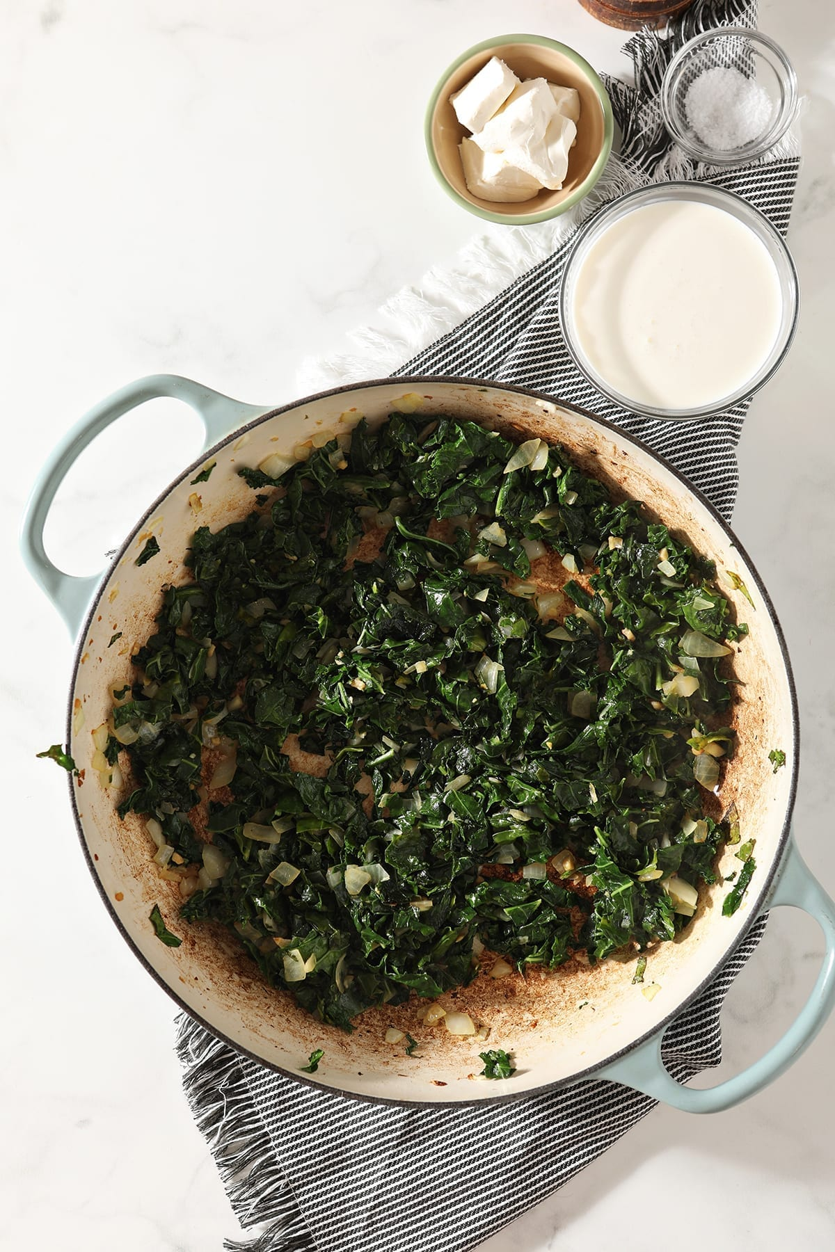 Overhead of sauteed kale and garlic in a pan sitting on a gray striped towel next to cream and cream cheese