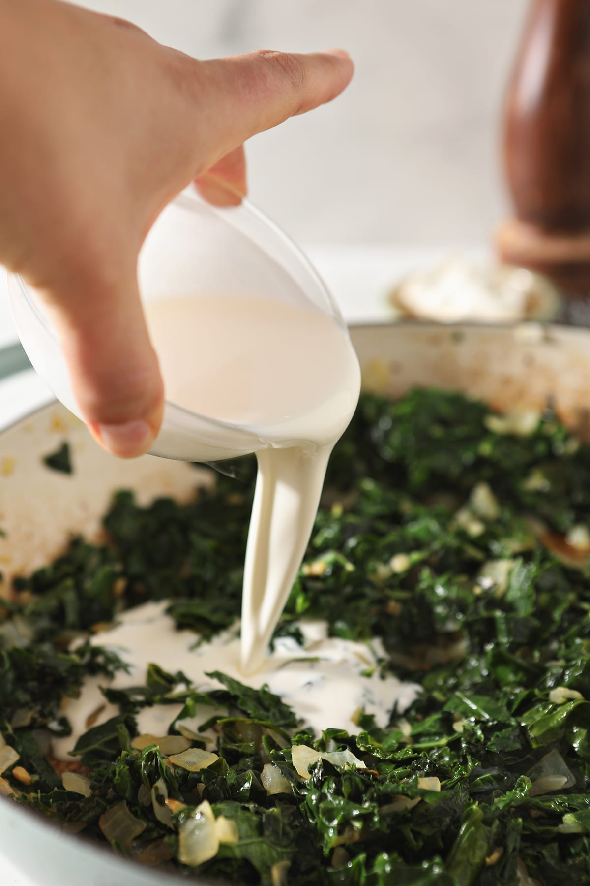 Cream pours on top of wilted kale in a pan