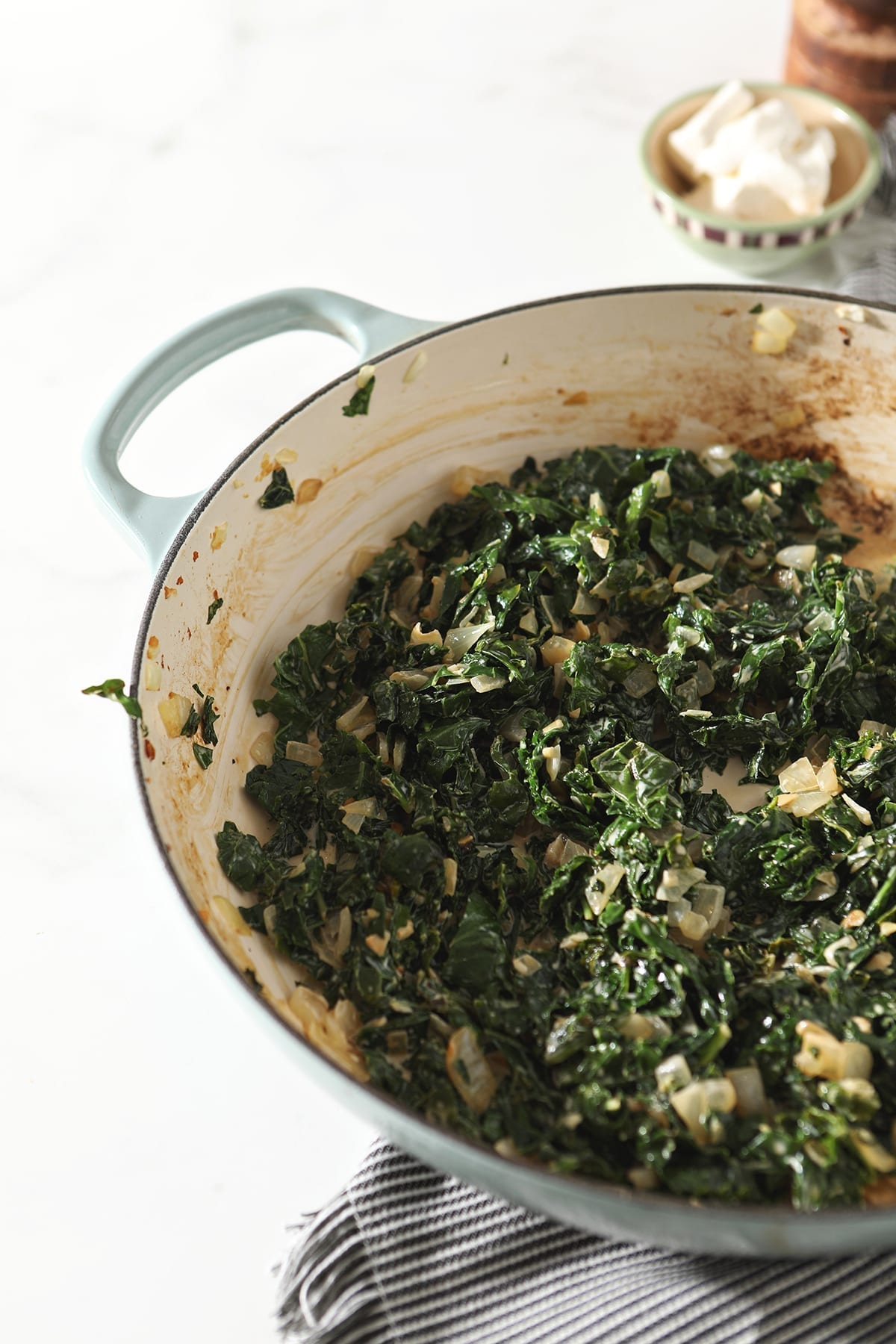 Kale with cream in a pan, before cream cheese is added