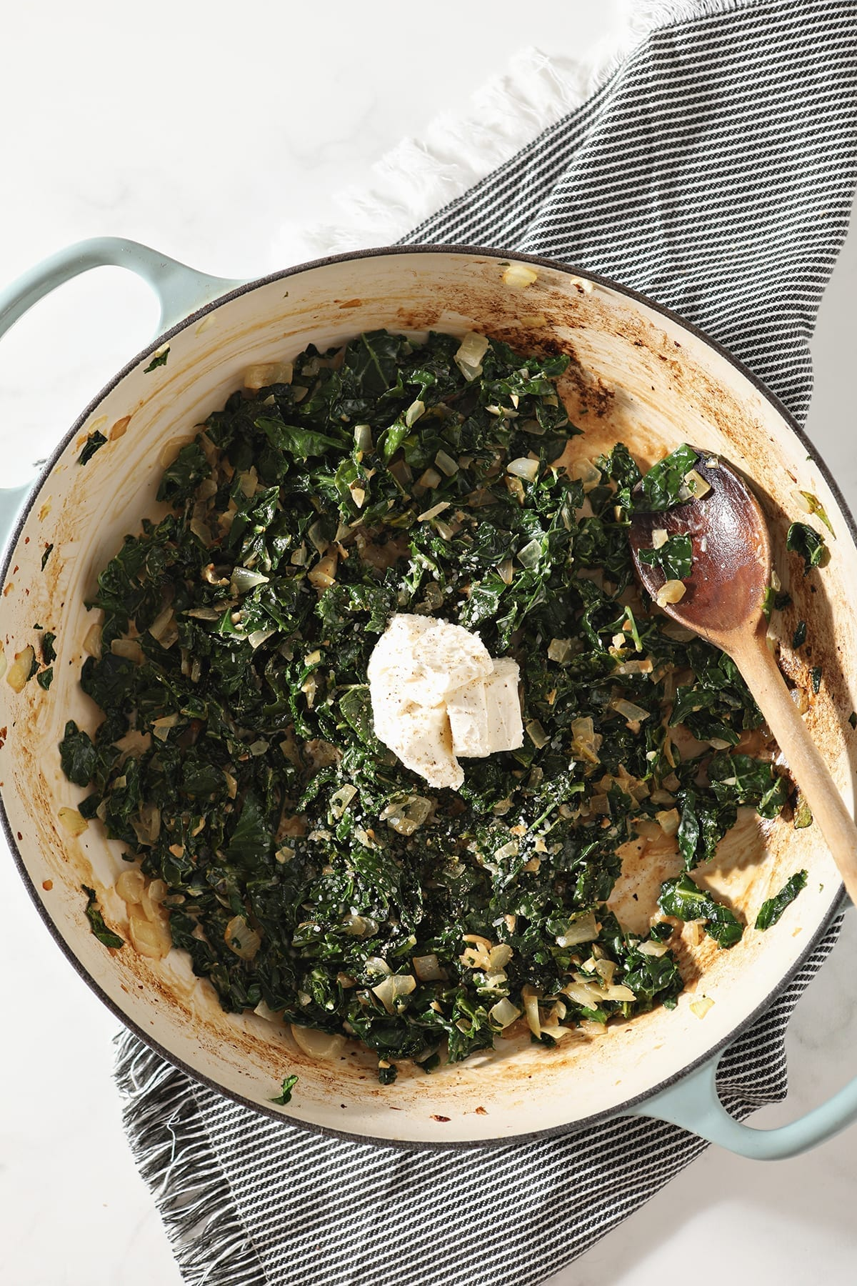 Cream cheese sits on top of wilted kale and cream in a pan, before stirring