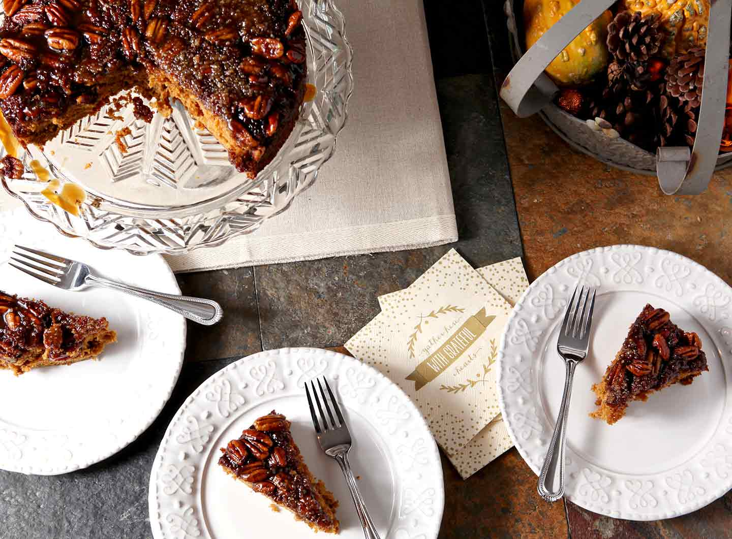 Three slices of Praline Pumpkin Upside Down Cake are served on a dark background