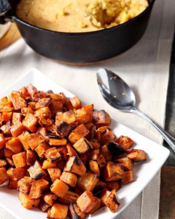 A white plate holds Bourbon Butter Sweet Potatoes with a skillet of cornbread in the background