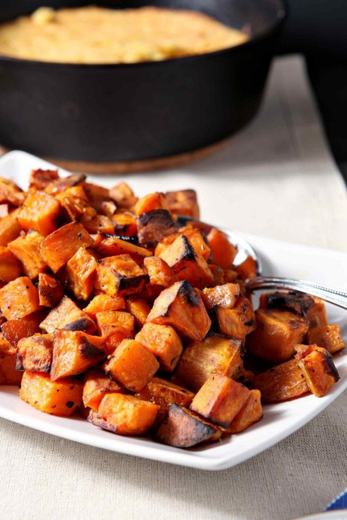 Close up of Bourbon Butter Sweet Potatoes on a white platter