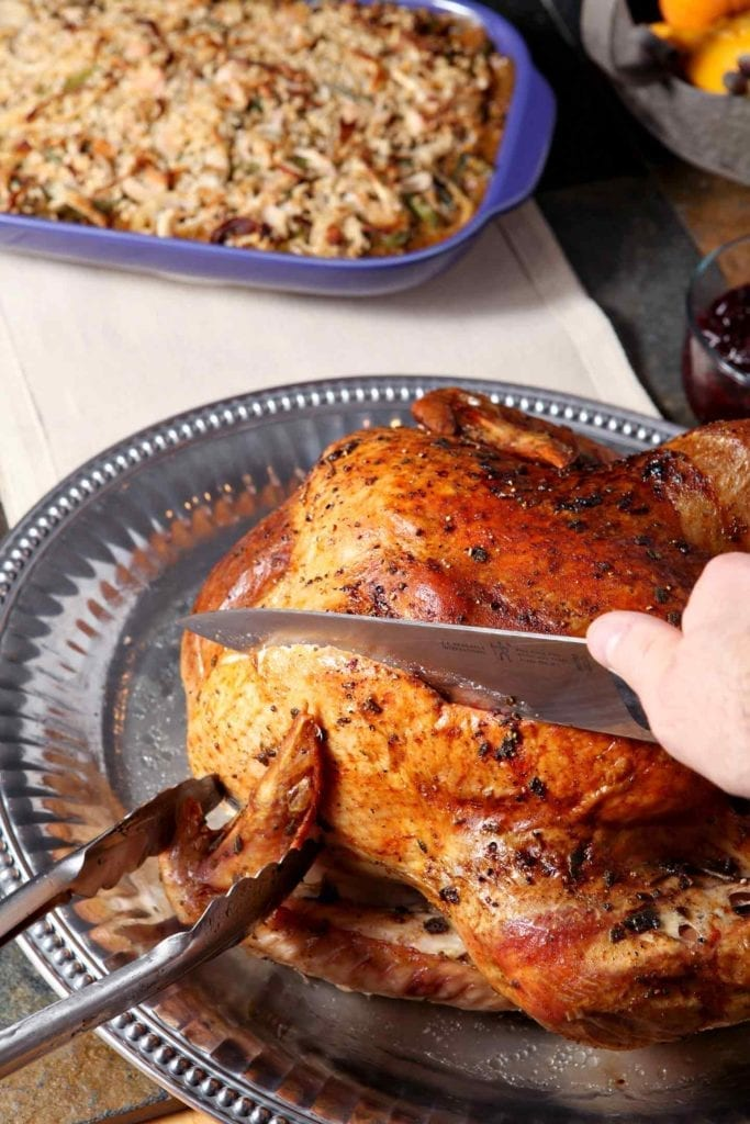 A whole roasted Browned Butter Sage Turkey is cut into with a knife.