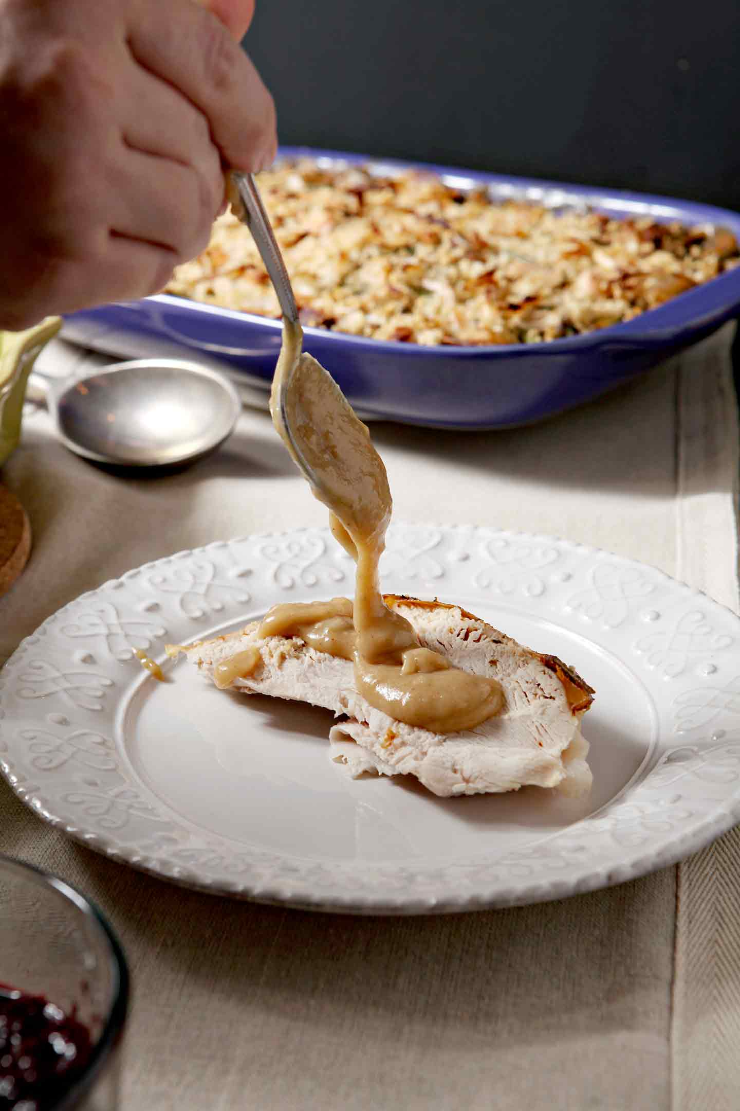 Gravy is drizzled on top of a slice of turkey breast on a plate