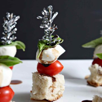 Caprese Skewers are the perfect easy appetizer to make for a crowd this holiday season! Crusty ciabatta bread serves as the base. Grape tomatoes, small mozzarella balls and fresh basil are layered onto the bread, then skewered with a festive toothpick. To finish the dish, drizzle reduced balsamic vinegar on top, and enjoy! Red and green, these simple but delicious Caprese Skewers are sure to be a winner at parties this season... and any season!