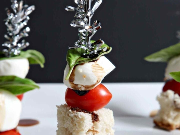 Colorful Caprese Skewers are served on a white platter.