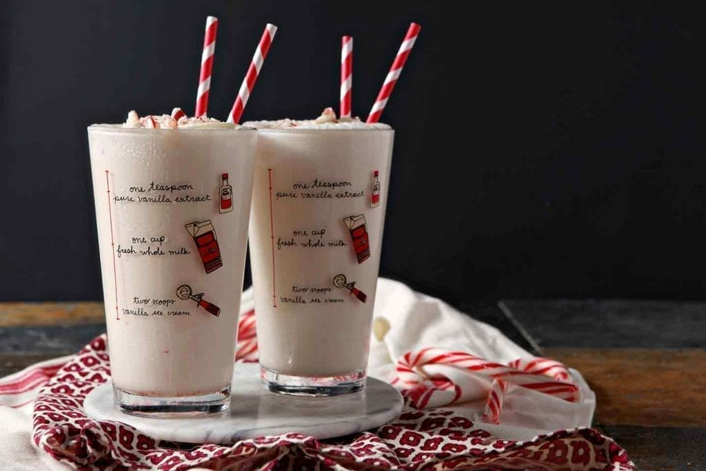 Two pint glasses holding pink milkshakes sit on a marble serving tray, ready for enjoying
