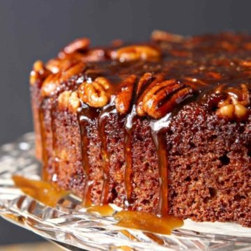 The topping drips down the side of a Praline Pumpkin Upside Down Cake before serving