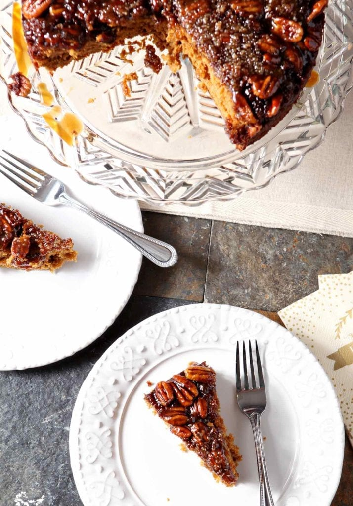 Two slices of Upside Down Pumpkin Cake on white plates, from above, next to the whole cake on a decorative glass plate