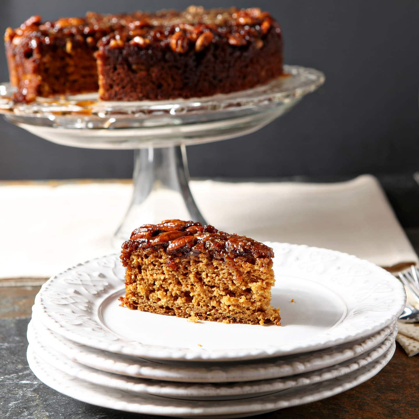 A slice of pumpkin cake with a praline topping sits on a white plate in front of a cake stand holding the rest of the dessert