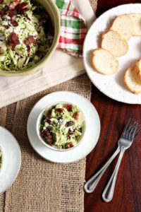 Two bowls of Cranberry Feta Brussels Sprout Salad with Candied Pecans and Warm Bacon Vinaigrette are seen from above