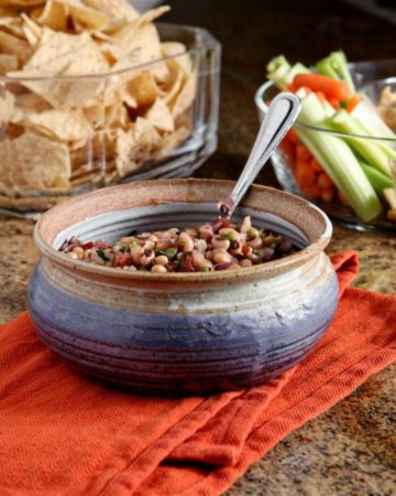 Bowl of Black Eyed Pea Dip served with chips and vegetable sticks