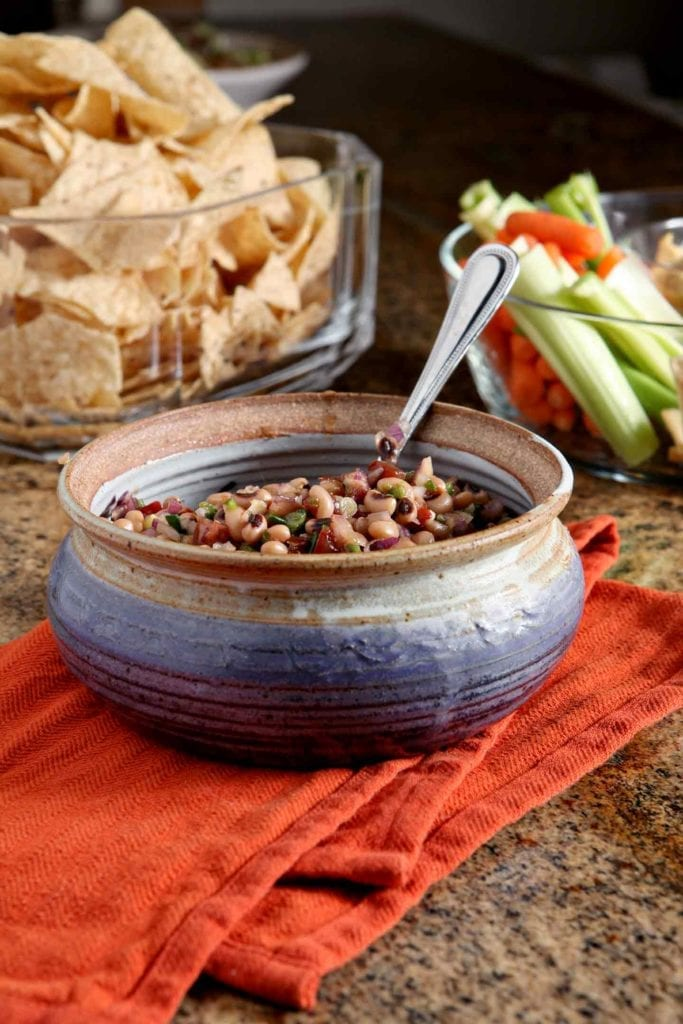 A bowl holding Black Eyed Pea Dip is served alongside other appetizers at a New Year's Day party