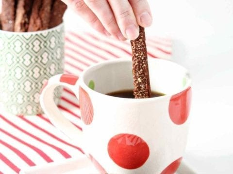 dipping gingerbread biscotti in coffee