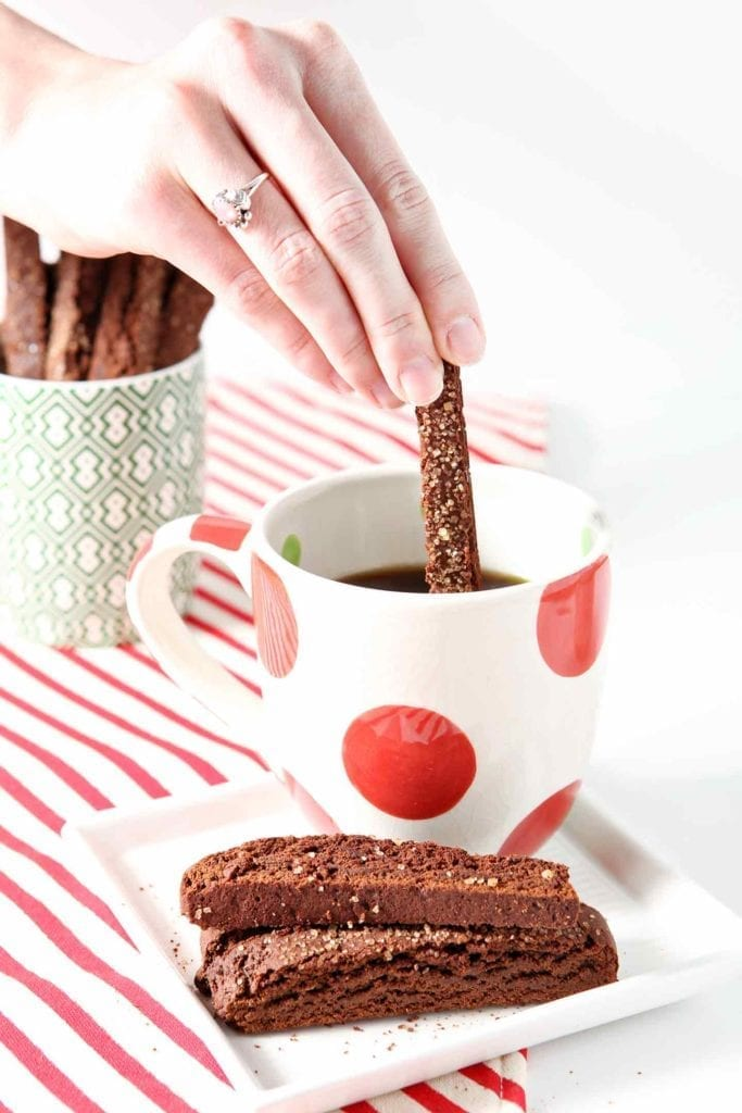 A woman dips a Chocolate Gingerbread Biscotti into a mug of coffee