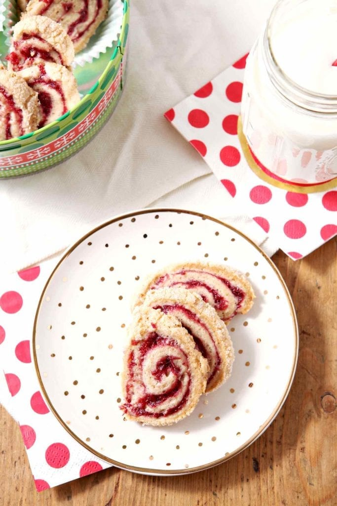 Celebrate the season with Cranberry Pinwheel Cookies! Mix up a classic tea cake dough, then slather with cranberry filling, studded with pecans, and roll into a pinwheel. Brush the rolled cookie log with an egg wash and sprinkle with sugar. Chill, then slice and bake until golden brown. Serve with milk or a favorite festive cocktail - if that's your thing! Tart, slightly sweet Cranberry Pinwheel Cookies are a festive cookie for Christmas parties. #spon #IncredibleBulkBinTreatExchange