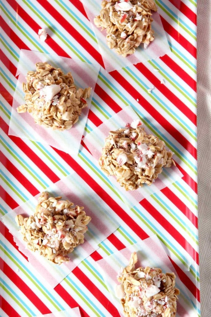Need a quick cookie recipe for the holidays that the whole family and Santa will adore? Mix up these super simple No Bake Peppermint Bark Cookies today! White chocolate and marshmallows melt together to form the base of this gluten-free cookie. When the mixture is melted, stir in crushed candy cane pieces and rolled oats. Scoop the no bake cookies onto a lined baking sheet and chill before consuming. Enjoy with a mug of cocoa this Christmas! #sweetestseasoncookies