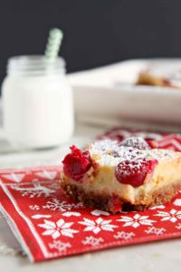 Dairy free Cranberry Orange Bars make a scrumptious seasonal dessert! A twist on the classic Lemon Bar, this sweet start with a crunchy homemade Graham cracker crust. Drizzle silky orange filling on top of the pre-baked crust, then sprinkle on fresh cranberries before baking. When these Cranberry Orange Bars come out of the oven, let cool, then dust with powdered sugar for the finishing touch. What a festive Christmas treat for the whole family! #sweetestseasoncookies