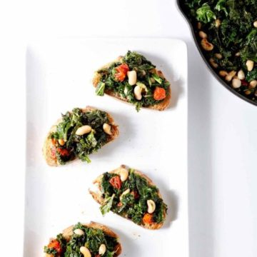 Break free of the winter entree doldrums and make veggie-filled Vegan Tuscan Kale Bruschetta tonight. This twist on a traditional bruschetta highlights Tuscan kale, cooked down with grape tomatoes and cannellini beans. The kale becomes marvelously wilty, the tomatoes blister and break apart, and the beans brown slightly before all three are served upon toasted bread. Vegan Tuscan Kale Bruschetta is a scrumptious dinner or appetizer for a crowd.