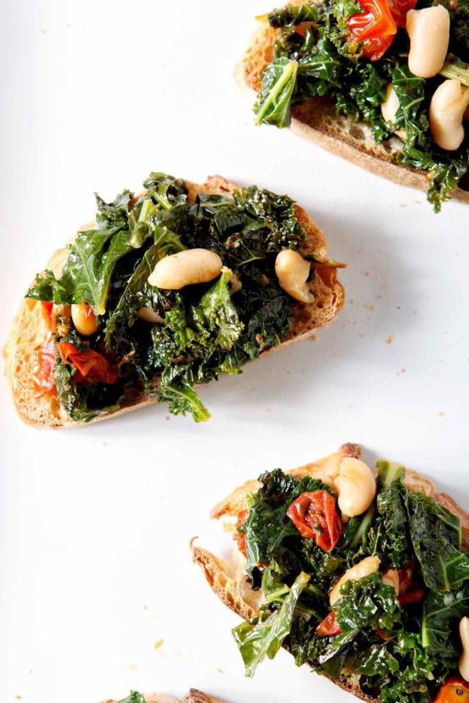 A close up of several Vegan Tuscan Kale Bruschetta sitting on a white platter
