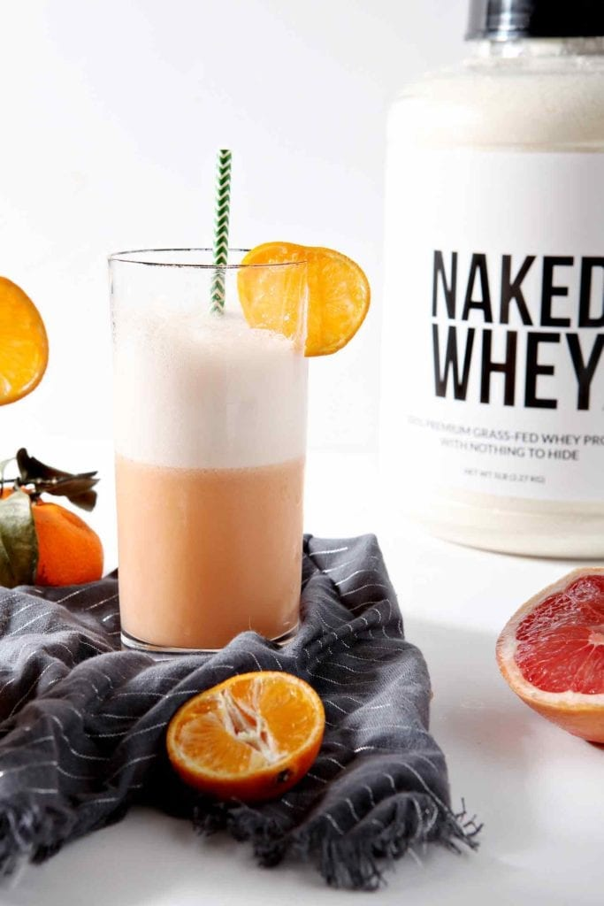 Blast the blues away by mixing up a Creamy Winter Citrus Smoothie! Naked Nutrition Grass Fed Whey Protein Powder acts as the base of this healthy smoothie. Blended with freshly squeezed pink grapefruit juice, orange juice and lime juice, it creates a deliciously fruity drink that works well in the mornings or afternoons. Not only it is tasty, but this Creamy Winter Citrus Smoothie boasts a ton of protein to fuel your body throughout the day. #ad