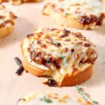 French Onion Bruschetta on a wooden serving platter