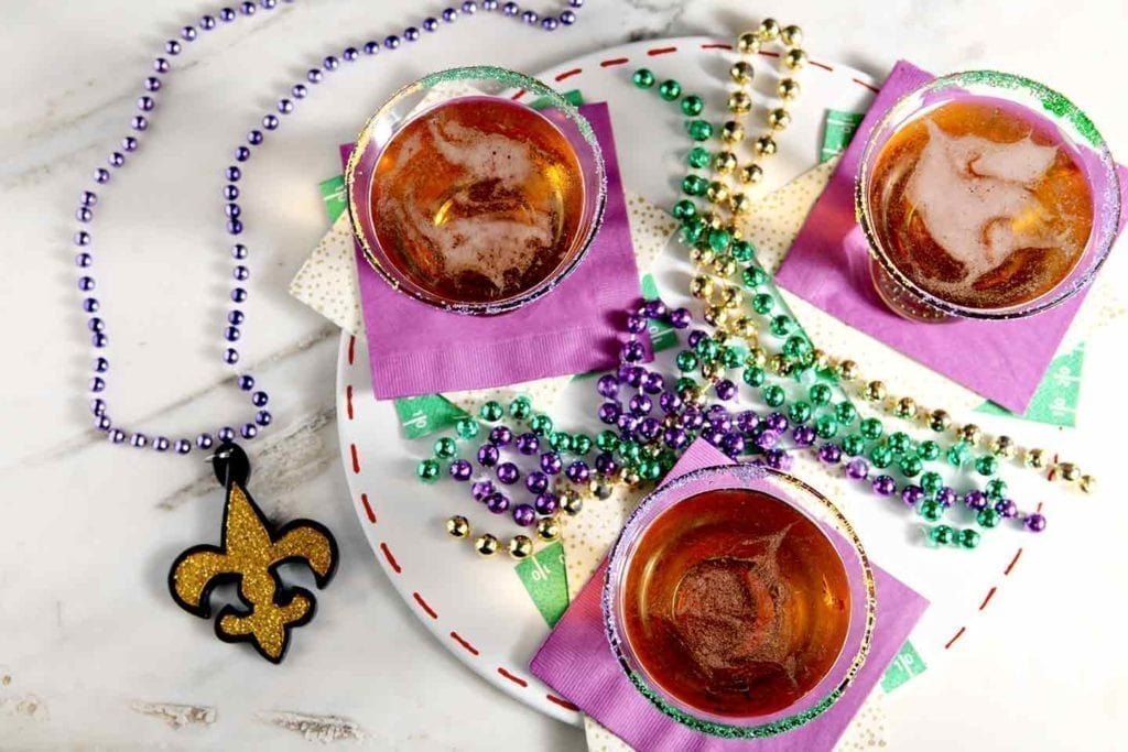 Overhead of three dessert martinis on purple napkins surrounded by purple, gold and green beads on marble