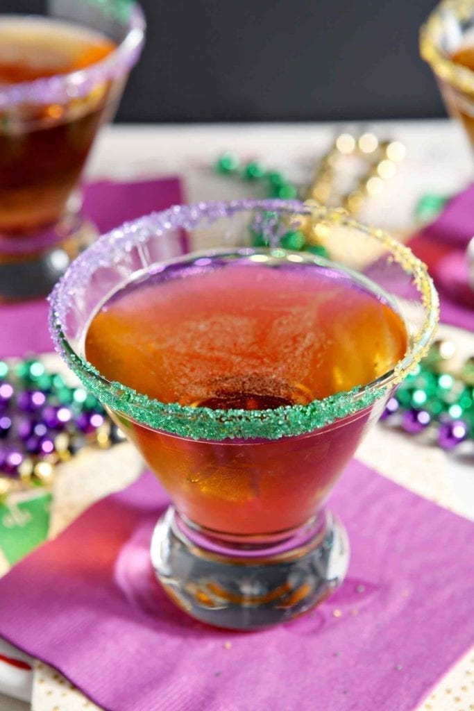 Close up of a king cake martini on a purple napkin, surrounded by festive mardi gras beads