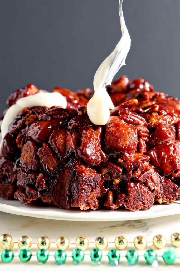 Cream cheese frosting is spread on top of monkey bread
