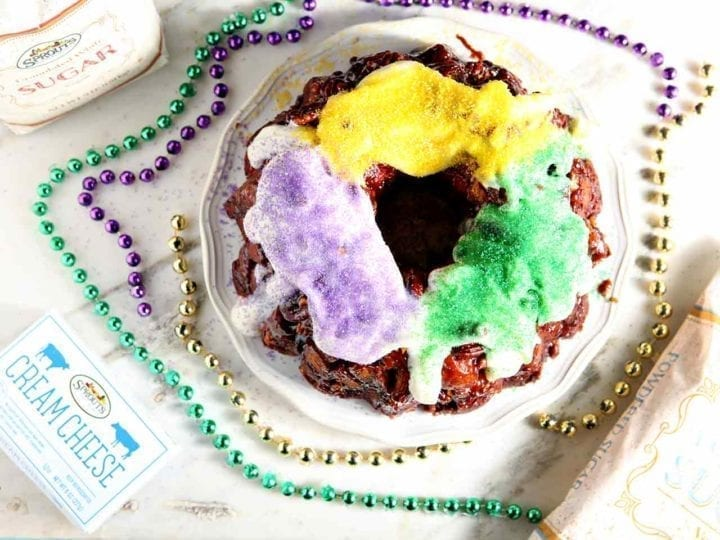 Overhead image of a cinnamon roll king cake on a marble slab next to cream cheese, powdered sugar and beads