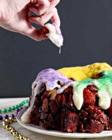 A woman pulls a piece of monkey bread king cake out off the cake