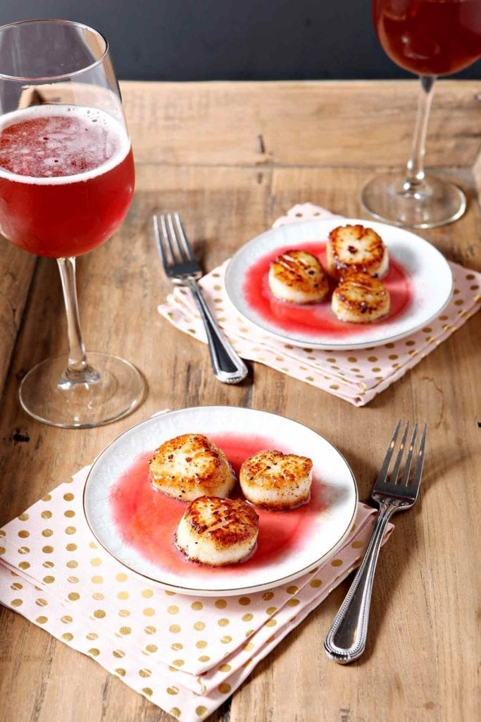 Two plates holding scallops with a red gastrique sit on a wooden tray next to a red drink