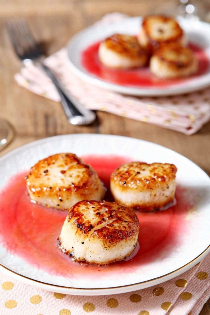 Close up of Seared Scallops with Raspberry Gastrique on a white plate
