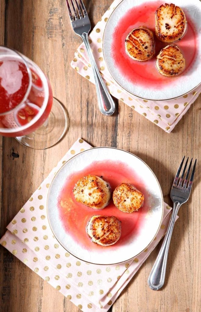 Overhead photo of Pan Seared Scallops with Raspberry Gastrique on a tray with pink drinks, napkins and forks