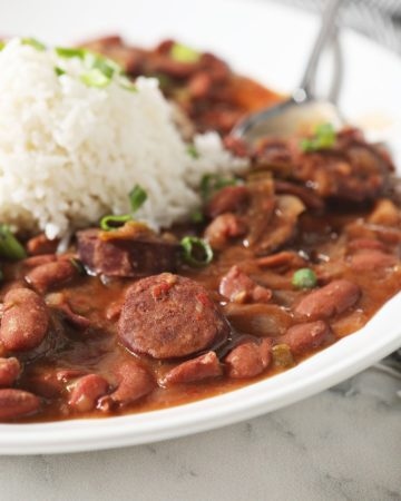 Sliced andouille sausage and red beans in a bowl with rice