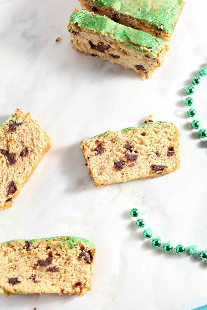 Several slices of a chocolate chip loaf cake sit on a marble surface next to a green set of beads