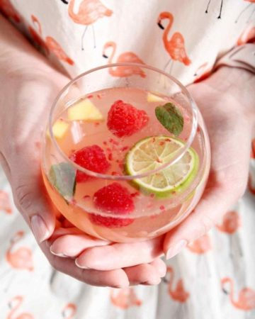 A woman in a flamingo shirt holds a glass of mango raspberry white wine sangria