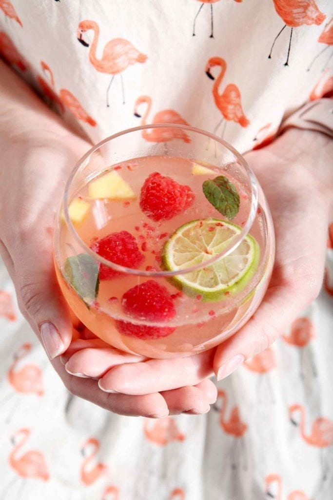 A woman, wearing a brightly colored flamingo shirt, holds a glass of Raspberry Mango Spring Sangria in her hands
