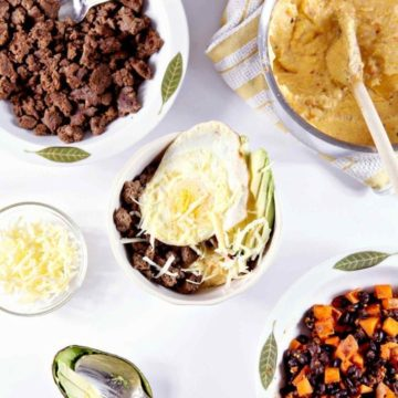 Southwestern Breakfast Burrito Bowl from above, with grits, ground turkey sausage, cheese, avocado, egg and a sweet potato hash on a white background